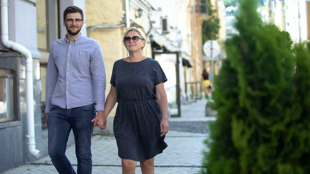 Mature woman walking on street with younger men, relations and connection