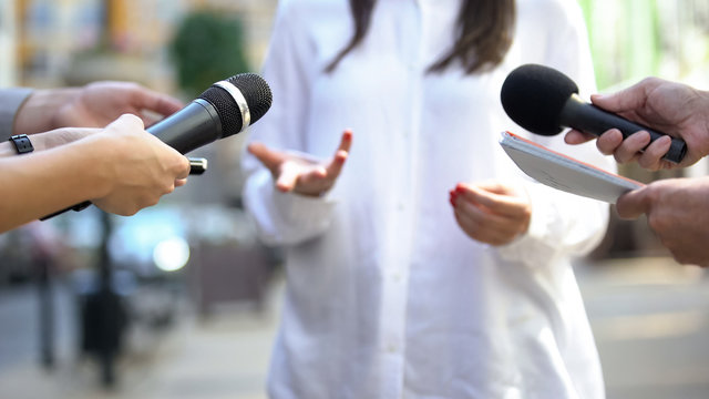 Female politician talking on media press conference, public relations, event