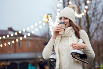 Papiers peints Glisse hiver Charming young woman in the Park near the ice rink. Smiling brunette with skates