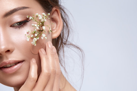gorgeous woman close-up with green plants under plaster on her cheek