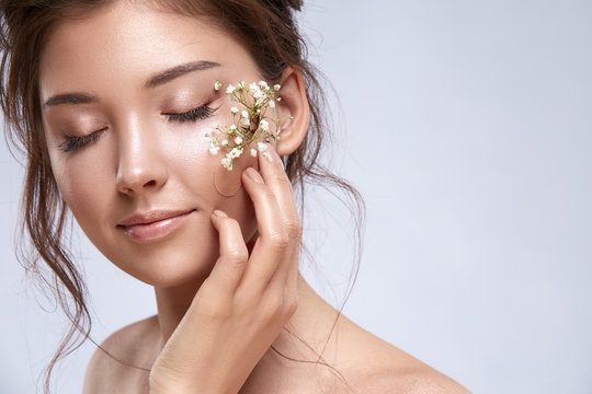 pretty female with nude make-up touching a cheek with plaster and flowers on it