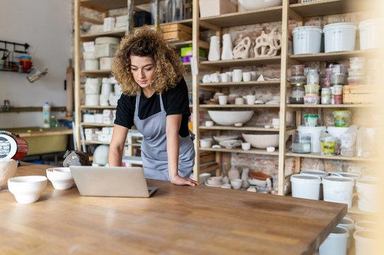 Woman pottery artist using laptop in art studio