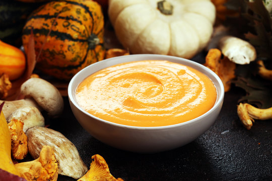 Roasted pumpkin and carrot soup with cream and pumpkin seeds on wooden background.