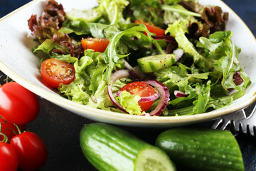 bowl of salad with vegetables and greens, with tomato, cucumber and onions on rustic table