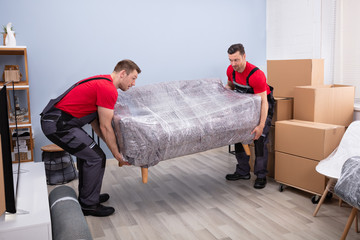 Male Movers Carrying Wrapped Sofa In New House