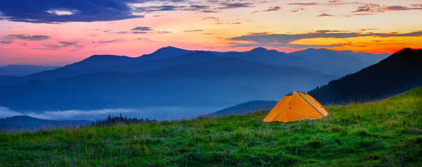 Photo sur Aluminium Camping Orange tent in the mountains at sunset