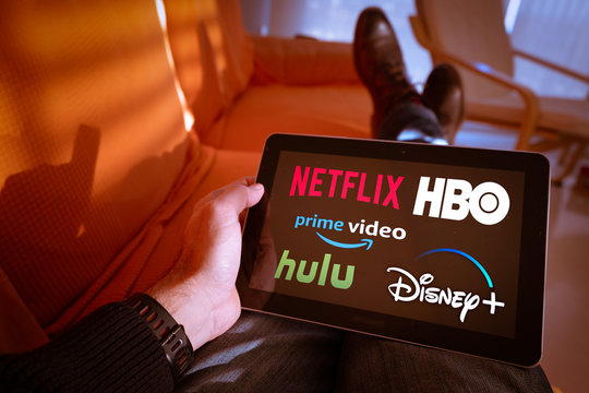 Barcelona, Spain. January 2019: Man holds a tablet with Netflix, hulu, amazon video, HBO and Disney+ logos on screen
