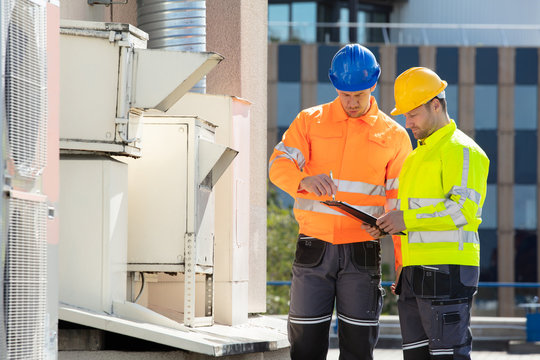 An Electrician Men Checking Air Conditioning Unit