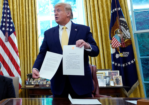 U.S. President Trump holds letter from China's President Xi Jinpingduring meeting with China's Vice Premier Liu at the White House in Washington