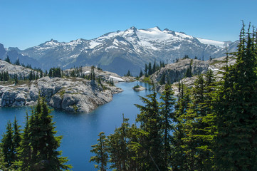 Robin Lake surrounded by granite and trees with snow-capped Mt. Daniel towering in the background under a clear sky in the Alpine Lakes Wilderness, Washington State, USA. Fotomurales