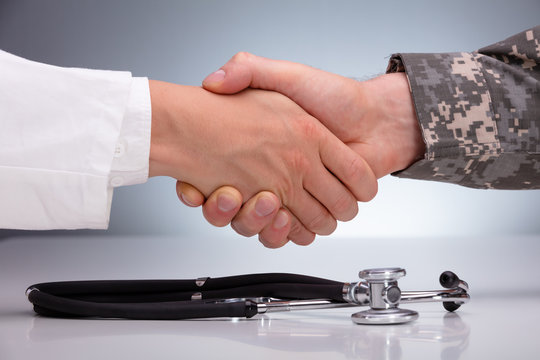 Doctor And A Military Man Shaking Hands Over The Stethoscope