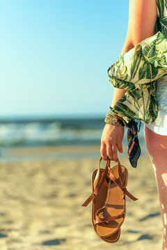 Woman holds brown leather sandals in her hand and looks at the sea