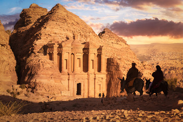 Monastery (Ad Deir) at sunset with silhouettes of Bedouins riding donkeys, Petra, Jordan