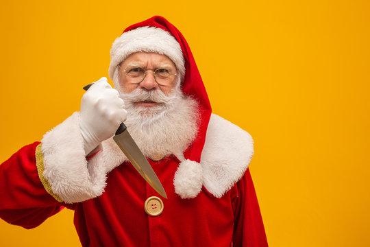 Santa Claus holding a knife. Evil Santa Claus concept. Murder.