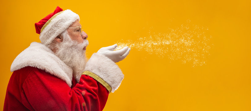 Holly jolly Xmas festive occasion Noel! Christmastime traditions! Santa in headwear, costume, white gloves expresses winter wish, surprise, fantasy, blizzard, snow, snowflakes, air kiss, blowing