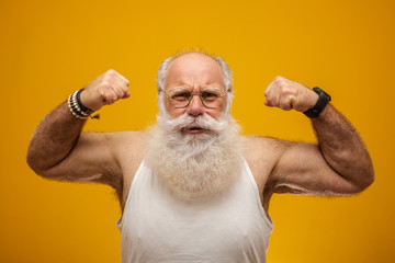 Old man with long white beard showing his strength with his arms