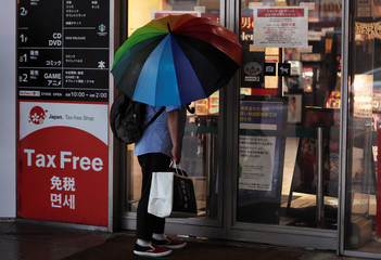 A man looks at a notice stating a shop is closed temporarily ahead of Typhoon Hagibis, in Tokyo, Japan
