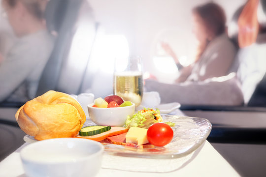 Airplane breakfast food in business class against passenger cabin interior blurred background. Side closeup view of aircraft meal starters on tray table. Luxury jet plane air travel service concept