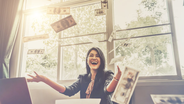 Happy businesswoman with around falling money in office