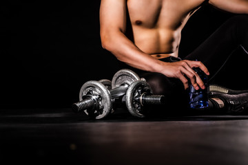 In de dag Ontspanning sport man at fitness gym club sitting relaxing after exercise with dumbbells on black backgrounds, fitness concept, sport concept