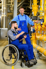 disabled worker in wheelchair in factory and colleague