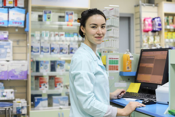Female pharmacist works in a pharmacy. Pharmacist at the computer in the pharmacy.