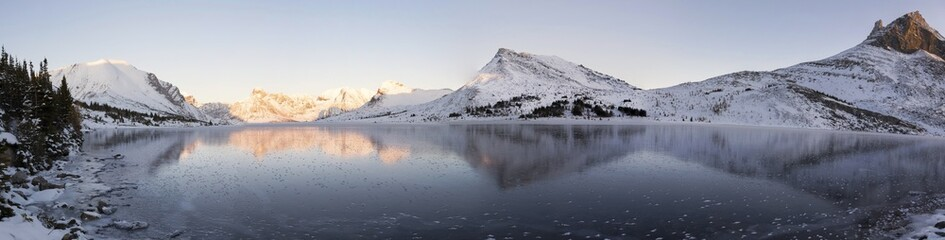 Wide Panoramic Landscape Snowy Mountain Peaks Reflected in Frozen Ptarmigan Lake Ice, Banff National Park Sunset, Canadian Rockies Alberta Canada