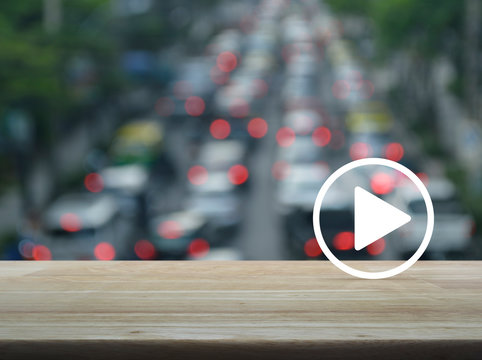 Play button on wooden table over blur of rush hour with cars and road, Business music online concept
