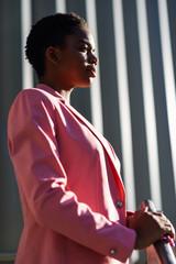 Black businesswoman standing near business office building.
