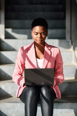 Black woman sitting on urban steps working with a laptop computer.