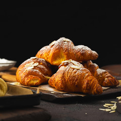 Breakfast croissant with chocolate on a dark stone background