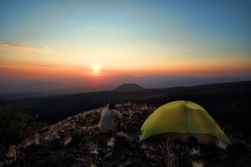 Hiker Overlooking Sunset From Wild Camp In Etna Park, Sicily