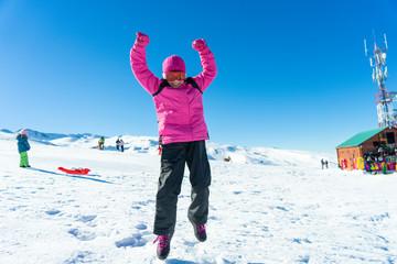 Little girl jumping on the snow at Sierra Nevada ski resort.