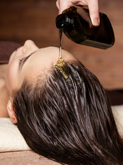 Obraz Cosmetologist pours balm for hair on head of  woman. Spa treatments. - fototapety do salonu