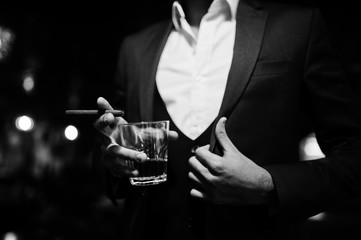 Close up hand of handsome well-dressed arabian man with glass of whiskey and cigar posed at pub.