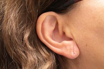 Female earlobe with piercing hole mark, ageing external ear skin