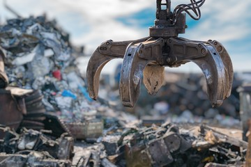 Close-up view on mechanical arm claw of crane at landfill.