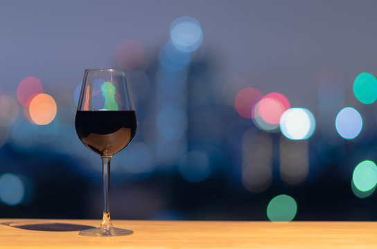 A glass of red wine on wooden table with colorful bokeh of city light and space for text.