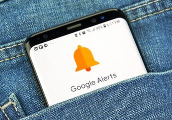 surveillance de la marque Google Alerts on a phone screen in a pocket