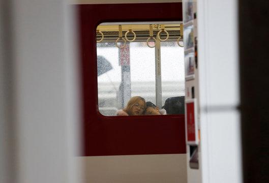 A couple sleeps inside a train during rain, ahead of Typhoon Hagibis, in Suzuka