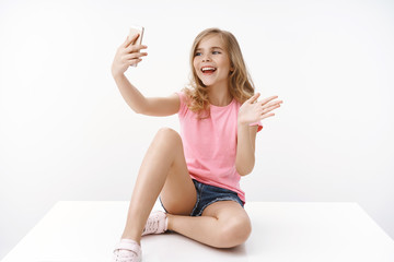 Cheerful enthusiastic happy blond teenage girl sitting crossed legs on floor, hold smartphone, record blog, communicate father abroad, taking selfie, waving hand greeting say hi mobile phone
