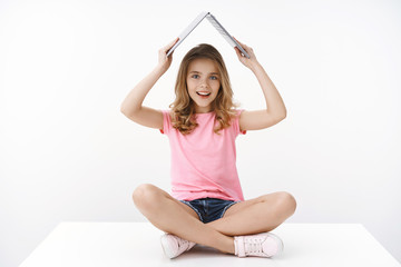 Smart cute blond caucasian little cheerful girl child sitting on floor amused excited, raise laptop under head like roof, smiling broadly, like studying at home online e-learning, white background