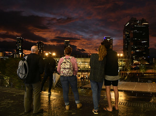 People look at clouds during sunset near Osaka Station, as typhoon 'Hagibis' approaches Japan