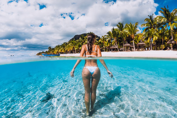 Young attractive woma posing in transparent blue ocean. Swimming in crystal water at Mauritius