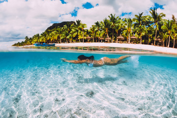 Young attractive woman swimming underwater in transparent blue ocean at Mauritius