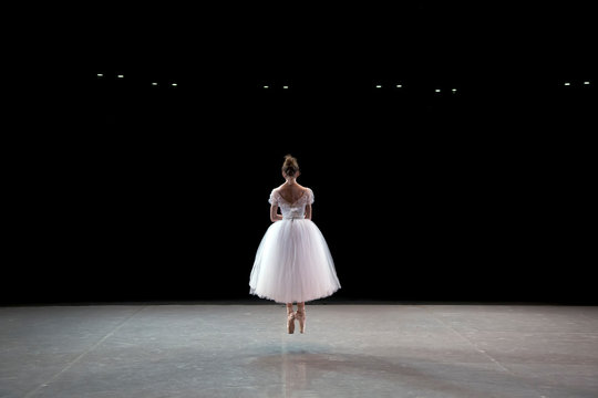 A ballerina dancing on a stage in a theater