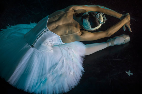 """A prima ballerina in the role of """"Odette"""" in the scene of the ballet """"Swan Lake"""" performs at the theater stage"""