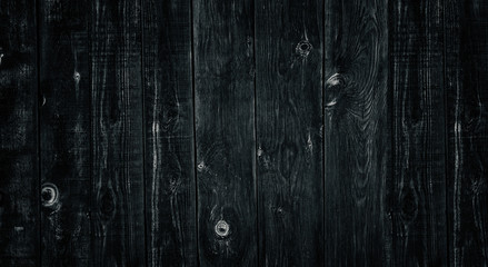 Old rough uneven wooden board dark widescreen texture. Black knotty weathered wood rural background
