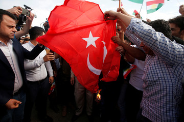 Iraqi Kurds burn the Turkish flag during a demonstration outside the United Nations building, against Turkey's incursion in Syria, in Erbil