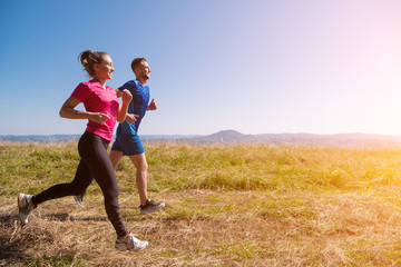 young couple jogging on sunny day at summer mountain